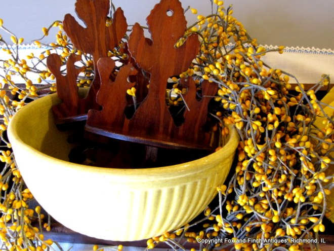 Charming plywood squirrel shelves sitting inside an antique yellow mixing bowl. The squirrels have tiny brass eyes.