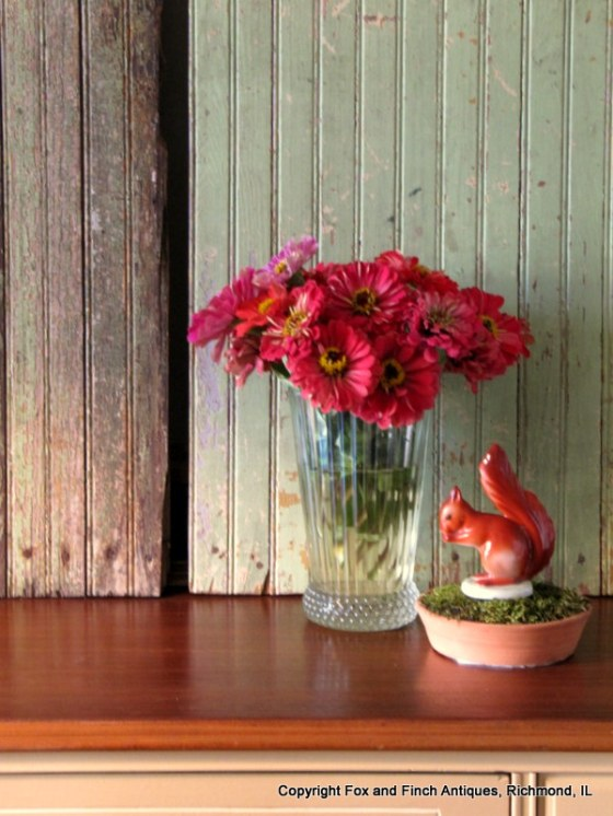 The last of the summer zinnias join a vintage Austrian squirrel.